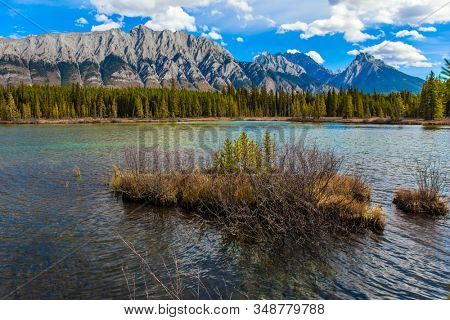 Magnificent mountain lake with emerald glacial water. Lakeshore overgrown with coniferous forests. Autumn day in Indian summer. The Canadian Rockies. The concept of ecological and photo tourism