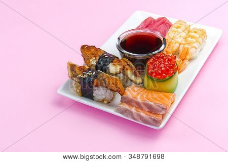 Traditional Japanese Sushi Set On A White Plate Isolated On A Pink Background. Tasty Set Of Sushi, N