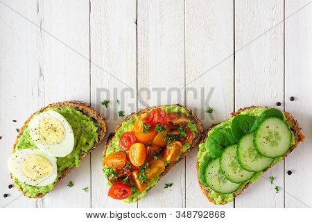 Healthy Avocado Toast Assortment With Eggs, Tomatoes And Cucumber Spinach. Bottom Border Flat Lay Ov