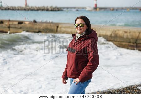 Middle-aged Woman Braving A Sunny Winter Or Spring Day At The Seaside Looking To Camera On A Breezy