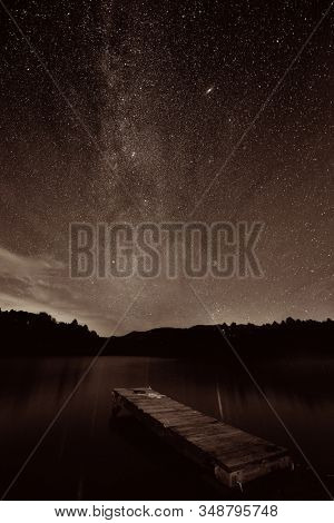 Milky Way over lake with dock in Stowe, Vermont.