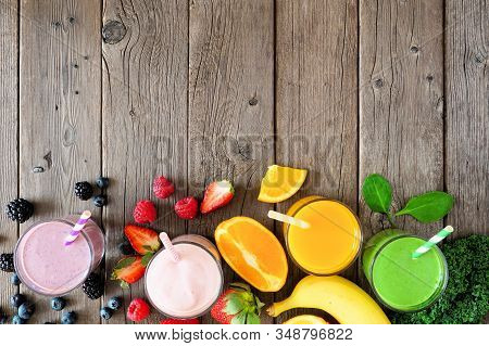 Assorted Healthy Smoothies. Top View Bottom Border Against A Rustic Wood Background. Blueberry, Stra