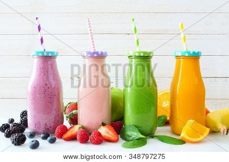 Various Healthy Smoothies In Bottles With Ingredients. Side View Against A White Wood Background. Bl