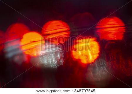 Abstract Bokeh Caused By Rain Drops Reflecting Onto Car Windscreen From Car Brake Lights And Night C