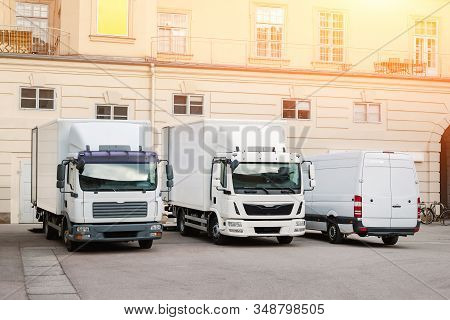 Different Small And Medium Courier Service Trucks And Van At Building Courtyard. City Delivery Cargo