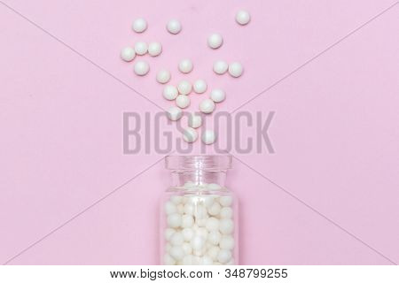 Homeopathic Globules Scattered From A Clear Glass Bottle On Light Pink Background, Alternative Homeo