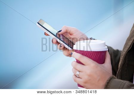 a busiess woman looking at cell mobile phone  and cup of coffeee