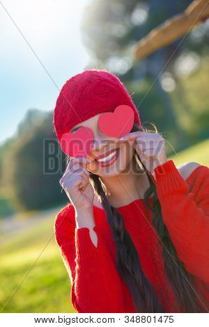 Woman in red with valentines hearts and smiling