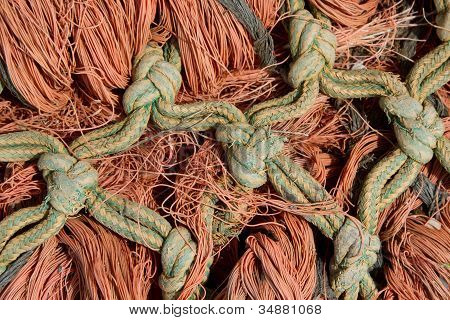A green and yellow knot linked rope interlaced with strands of orange rope. poster