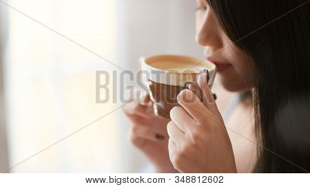 Close Up View Of A Woman Drinking Morning Coffee While Standing In Living Room With Sunlight Morning