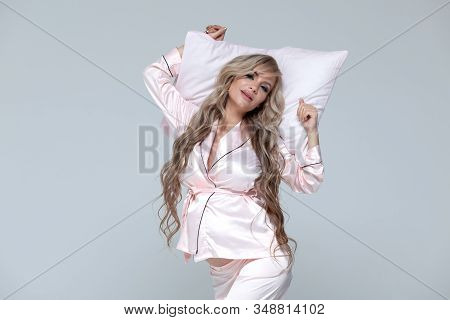 Young Beautiful Pregnant Woman In Pink Pajamas With Pink Pillow. Lying On Pillow. The Concept Of Sty