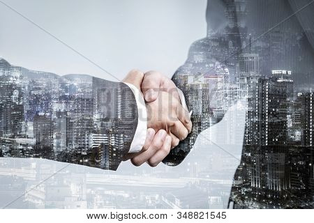 Double Exposure Of Business Partnership Handshake And Modern City , Successful Business Greeting Or