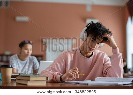 Pensive teenage student with headphones looking through page of manual before rewriting information in his notebook