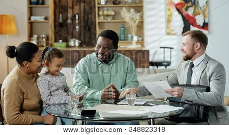 Group of cheerful ethnic couple with daughter and adult bearded agent gathering at table to discuss real estate mortgage