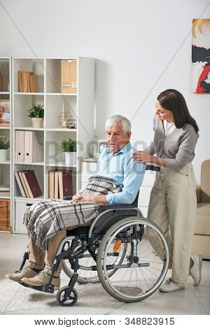 Young female care giver talking to grey-haired senior male pensioner sitting in wheelchair while staying at home