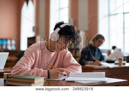 Clever guy in casualwear rewriting information from book in his copybook while sitting by desk in college library
