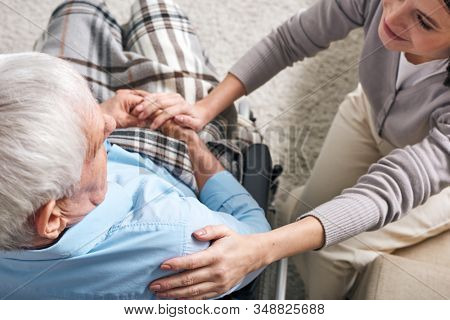 Young supportive female caregiver sitting by senior man in wheelchair and keeping her hand on his shoulder while comforting him