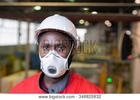 Portrait of Afro-American builder in respirator and hardhat standing at construction site