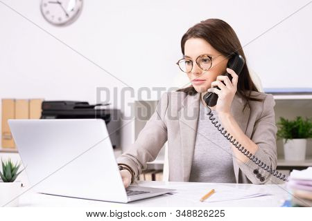 Serious attractive young secretary in glasses answering phone call while searching for information on laptop in office