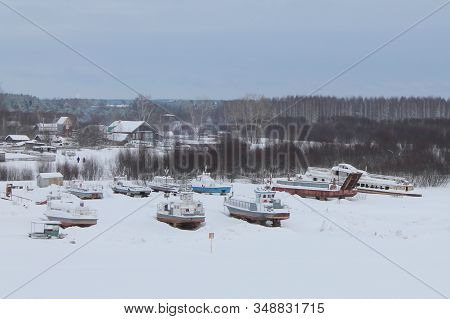 Snow Covered Landing Stage With Ships On Background Of Wooden Houses And Forest. Frozen River Surfac