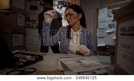 Forensic Scientist Woman In Gloves Examining The Evidence Bullet, Finding Clue