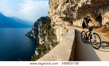 Cycling woman riding on bike at sunrise mountains and Garda lake landscape. Cycling MTB enduro flow sentiero ponale trail track. Outdoor sport activity.