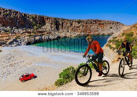 Cycling woman and man on electric bikes to wild beach with turquoise water and off-road  access . Couple cycling MTB enduro trail track. Outdoor sport activity.