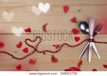 Valentine Concept. Fork, Knife And Tablespoon Tied With Red Pearls. Hearts And Petals Bokeh.invitati