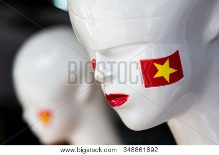 Mannequins in a clothes shop window with Vietnamese flags stuck on their faces, Hanoi, Vietnam, South East Asia