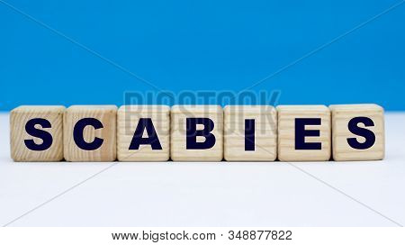 Concept Word Scabies On Cubes On A Blue Background