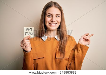 Young beautiful blonde woman holding pay taxes to goverment reminder over yellow background very happy pointing with hand and finger to the side