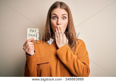 Young beautiful blonde woman holding pay taxes to goverment reminder over yellow background cover mouth with hand shocked with shame for mistake, expression of fear, scared in silence, secret concept