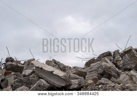 A Pile Of Large Gray Concrete Fragments With Protruding Fittings Against A Cloudy Sky.