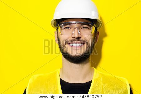 Studio Portrait Of Young Smiling Man Architect, Builder Engineer, Wearing Construction Safety Hard H