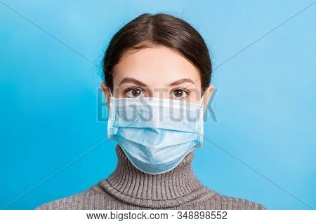 Portrait Of Young Woman Wearing Medical Mask At Blue Background. Protect Your Health. Coronavirus Co
