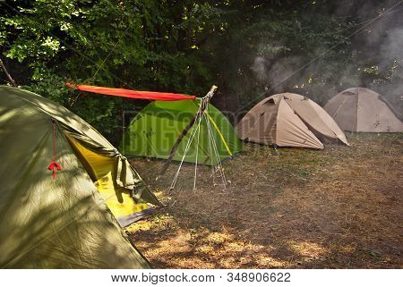 Camping Tent. Orange Hammock Stretched Between Tents. Smoke Campfire Over Tents.