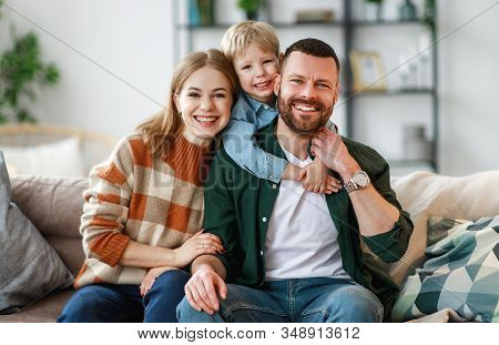 Happy Family Mother Father And Kid Son At Home On The Couch