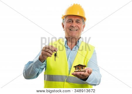 Old Male Builder With Trustworthy Expression Holding Small Wooden House And Keys Isolated On White S