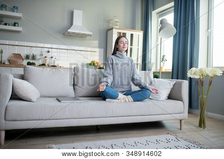 Young Girl In A Grey Sweater Meditating In A Lotus Pose