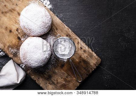 Top View Of Two Donuts Covered With Powdered Sugar On The Wooden Cutting Board And Stony Worktop.
