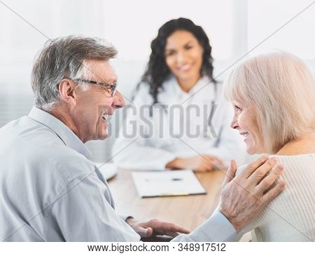 Heathcare Concept. Back View Of Happy Senior Husband Comforting His Wife During Consultation With Me