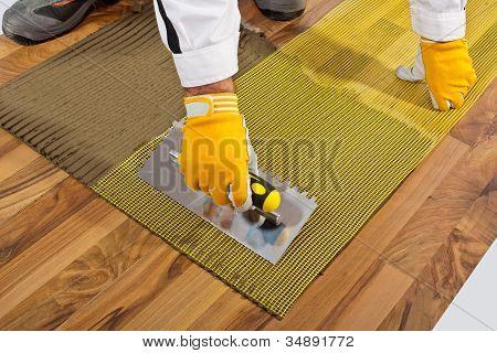 Applies Tile Adhesive On Wooden Floor With Reinforce Fiber Mesh