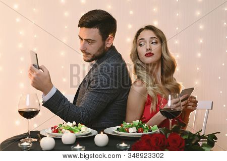 Mistrust Concept. Curious Woman Peeking Into Boyfriends Smartphone Over Shoulder, Trying To Read His