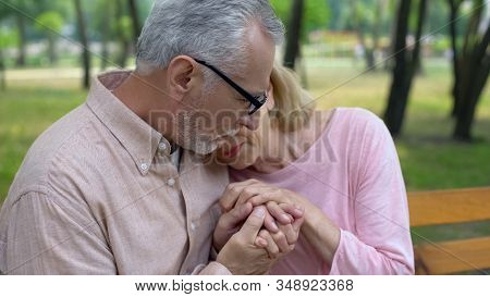 Male Pensioner Holding Sad Wife Hands, Health Problem, Spouse Support, Care