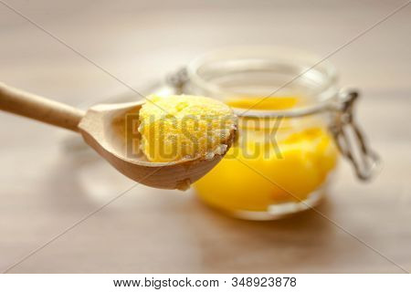 Ghee Clarified Butter Desi Yellow Color In Glass Jar With Spoon Made From Wood On Natural Wooden Bac