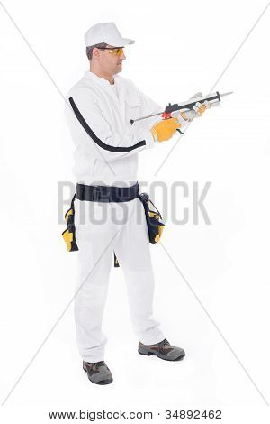 Construction Worker In White Overalls Holding A Gun With Silicone On A White Background