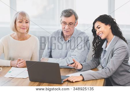 Real Deal. Older Couple Considering New Home Purchase Talking With Estate Agent Who Showing Them Lap