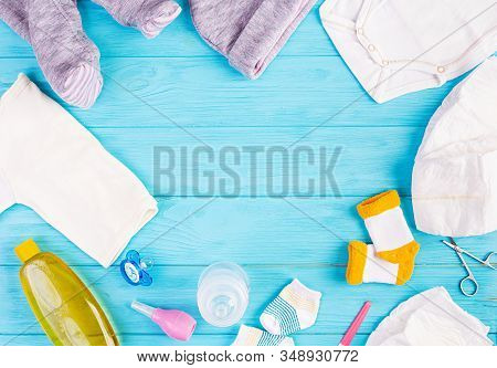 Baby Clothes And Other Stuff For Child On Blue Background. Newborn Baby Concept. Top View