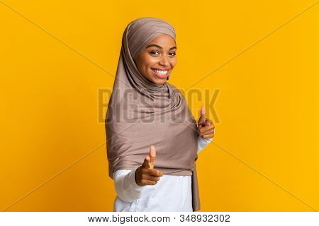 Gotcha. Smiling Black Muslim Woman In Headscarf Pointing Fingers At Camera, Posing Over Yellow Backg