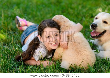 Lovely Photo Of Smiling Child Hugging A Puppy